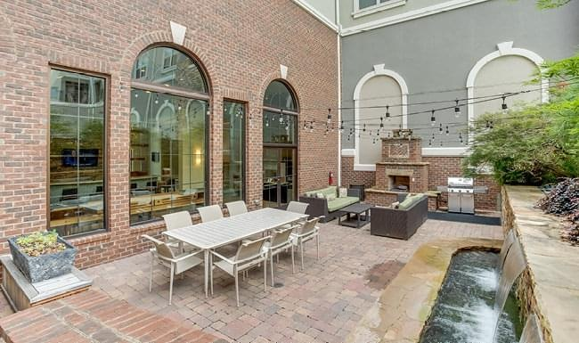 outdoor patio with stringed lighting, fireplace, grill area and water features
